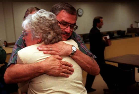 Dennis Huber hugs his wife, Ione, with the empty jury box in the